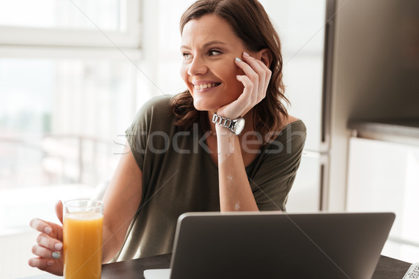 Smiling casual woman sitting by the table on kitchen Stock photo © deandrobot