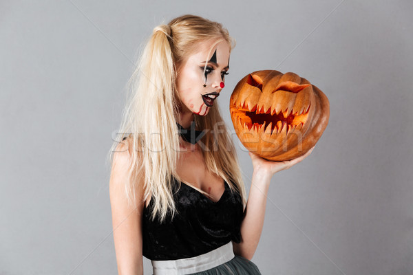 Pretty blonde woman in halloween make up holding carved pumpkin Stock photo © deandrobot