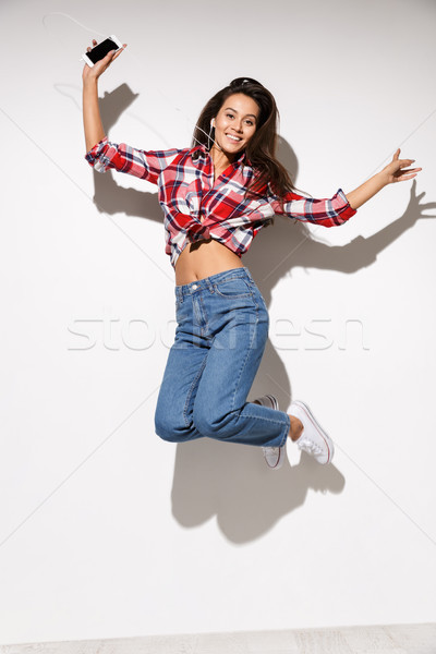 Young beautiful brunette women jumping and listening to music fr Stock photo © deandrobot