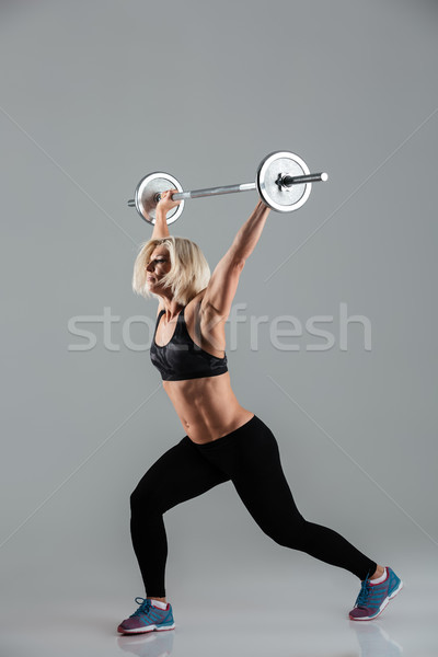 Full length portrait of a confident strong muscular adult sportswoman Stock photo © deandrobot