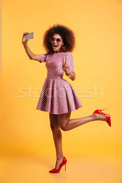 Full length portrait of a cheery afro american woman Stock photo © deandrobot