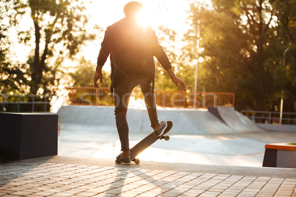 African skateboarder skating on a concrete skateboarding ramp Stock photo © deandrobot