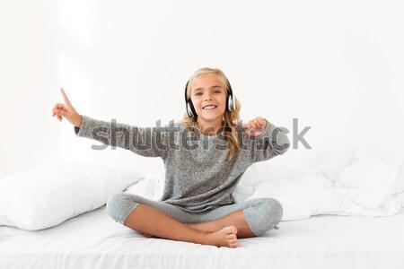 Vrolijk blond meisje grijs pyjama luisteren naar muziek Stockfoto © deandrobot