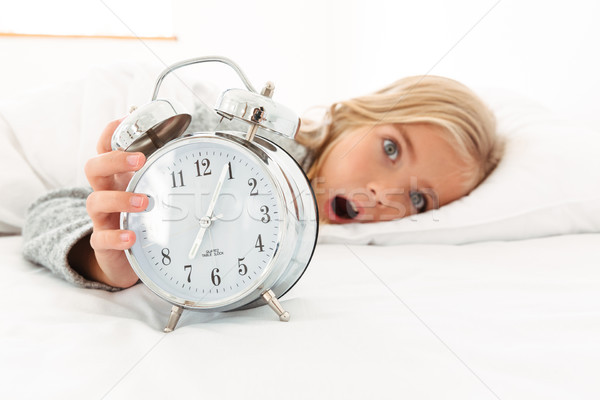 Portrait of a shocked cute little girl holding alarm clock Stock photo © deandrobot