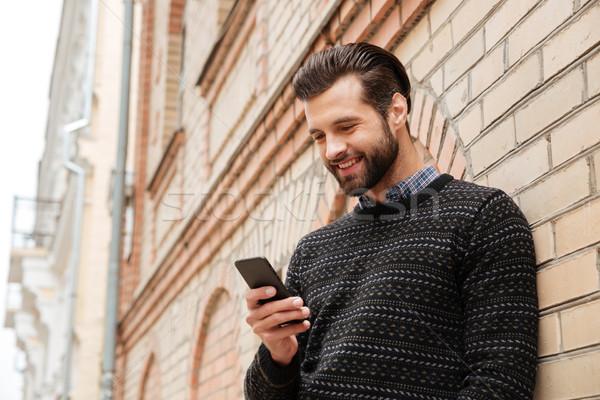 Ritratto felice bell'uomo maglione cellulare piedi Foto d'archivio © deandrobot