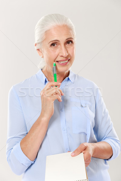 Happy woman with pen and notebook looking camera and smiling Stock photo © deandrobot