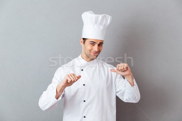 Handsome young cook in uniform pointing to himself. Stock photo © deandrobot
