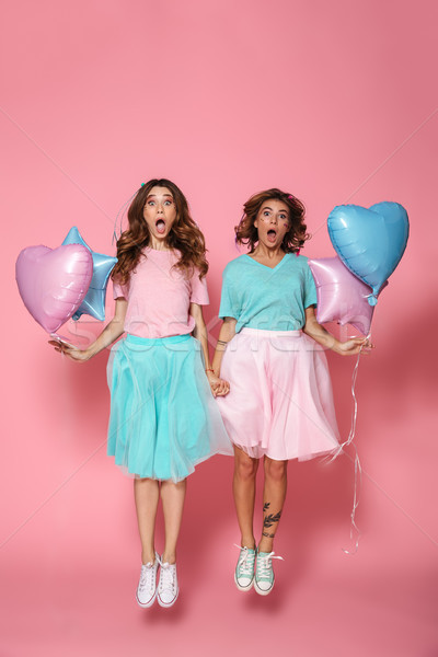 Full length portrait of two shocked female friends with balloons Stock photo © deandrobot