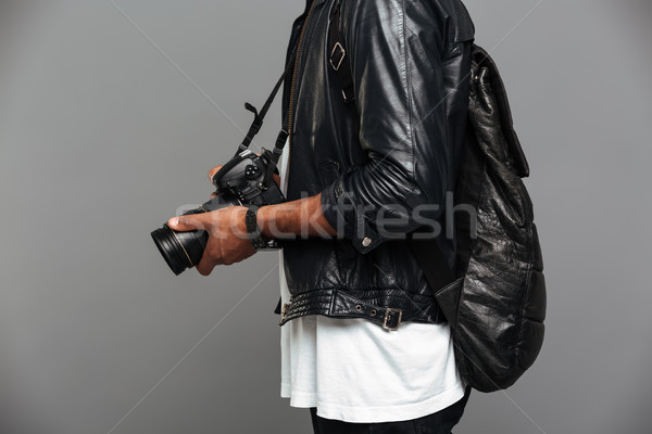Cropped photo of stylish african man with backpack holding photo Stock photo © deandrobot