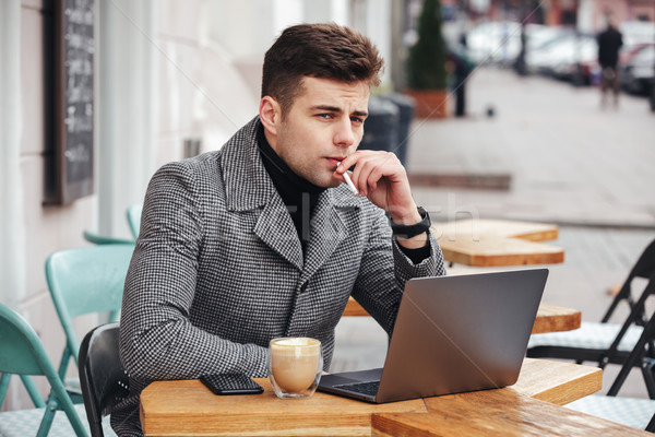Good-looking caucasian guy with brooding look sitting in cafe ou Stock photo © deandrobot