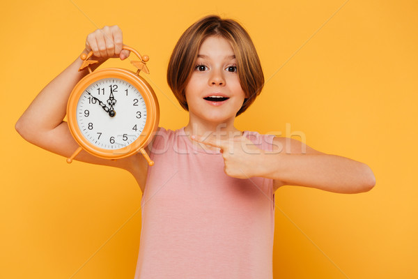 Happy girl pointing with finger at alarm clock isolated Stock photo © deandrobot