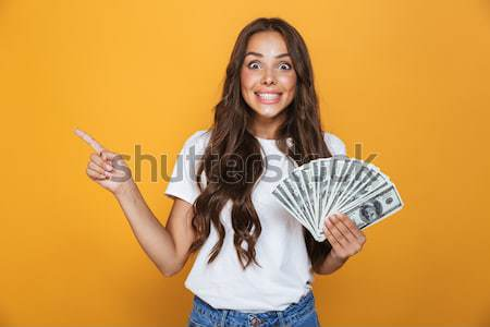 Smiling woman in sweater holding money and copyspace on palm Stock photo © deandrobot