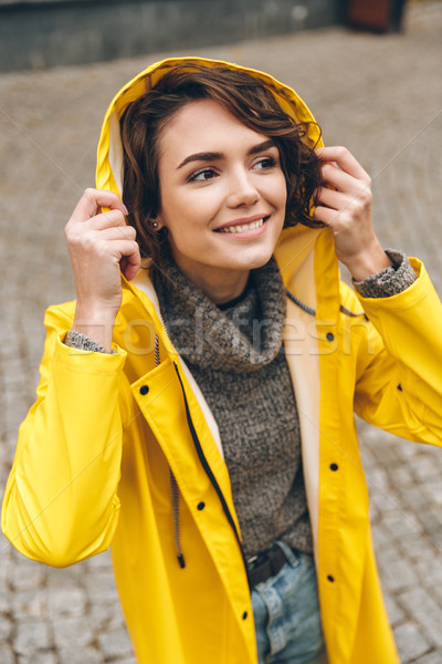 Caucasian joyous female in yellow raincoat wearing hood on and e Stock photo © deandrobot