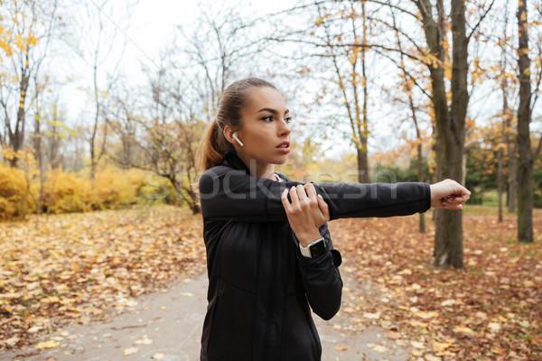 Portré csinos fitnessz lány fülhallgató nyújtás Stock fotó © deandrobot