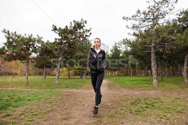 Portrait of a pretty fitness girl in earphones running Stock photo © deandrobot