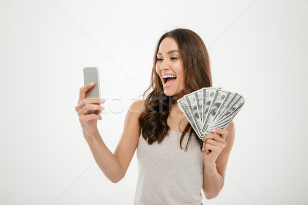 Portrait of happy joyous female 30s demonstrating lots of money  Stock photo © deandrobot