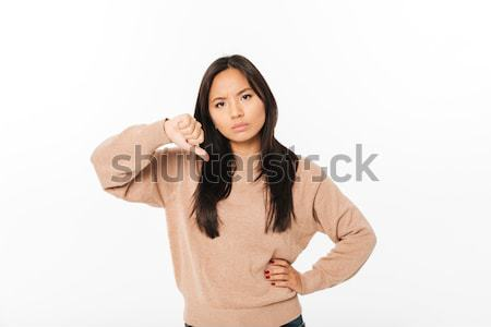 Asian displeased lady showing thumbs down. Stock photo © deandrobot