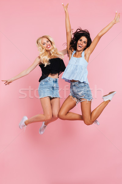 Full length image of two happy friends jumping in studio Stock photo © deandrobot