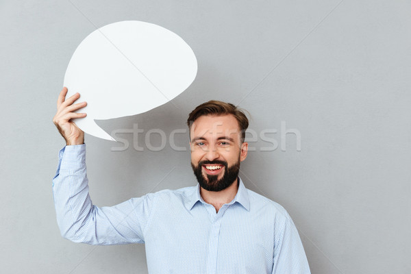 Happy bearded man in business clothes holding blank speech bubble Stock photo © deandrobot