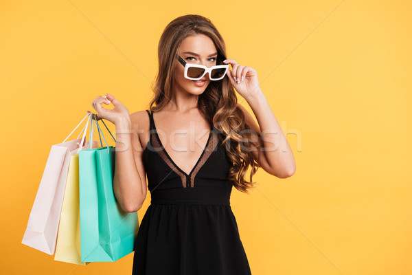 Serious young lady in black dress holding shopping bags. Stock photo © deandrobot