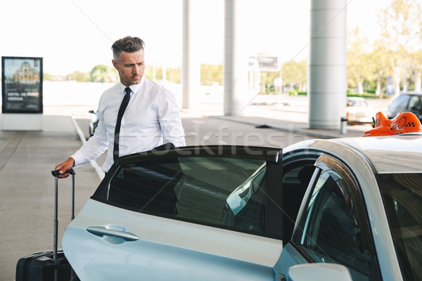 Handsome mature businessman getting in taxi Stock photo © deandrobot