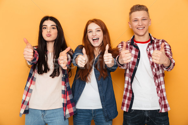 Group of smiling school friends showing thumbs up Stock photo © deandrobot