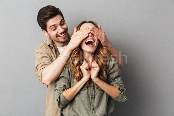 Portrait of a happy young couple , man covering Stock photo © deandrobot
