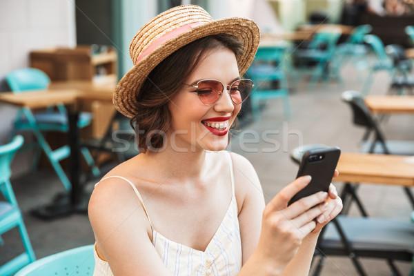Vrolijk vrouw jurk strohoed smartphone vergadering Stockfoto © deandrobot