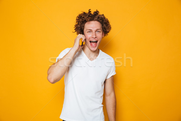Photo of brunette joyous guy with curly hair talking on smartpho Stock photo © deandrobot