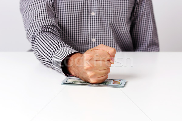 Closeup image of fist on a bills of dollars  Stock photo © deandrobot