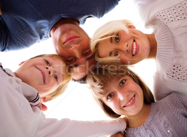 Happy family looking down at camera Stock photo © deandrobot