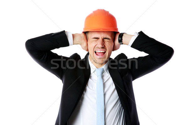 Businessman in helmet covering his ears over white background Stock photo © deandrobot