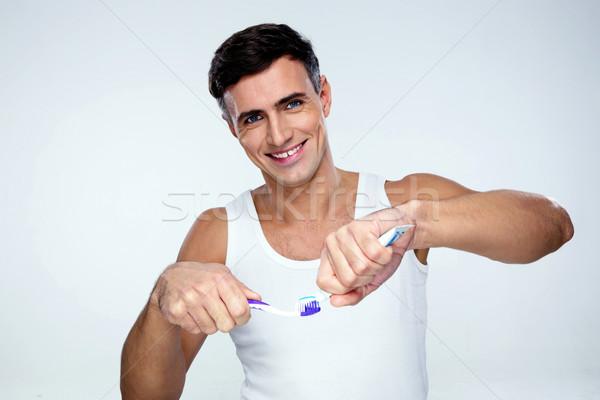 Boldog férfi fogkrém fogkefe szürke háttér Stock fotó © deandrobot