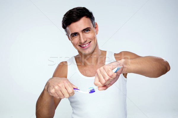 Gelukkig man tandpasta tandenborstel grijs achtergrond Stockfoto © deandrobot