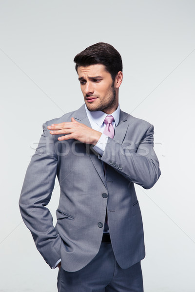 Businessman shakes off something from his shoulder  Stock photo © deandrobot