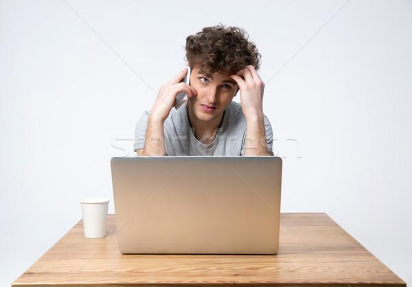 Dalgın genç oturma tablo dizüstü bilgisayar konuşma Stok fotoğraf © deandrobot