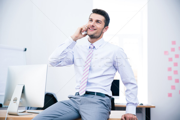 Happy businessman talking on the phone in office Stock photo © deandrobot