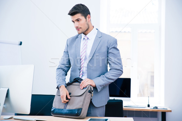 Handsome businessman closing bag on the table Stock photo © deandrobot