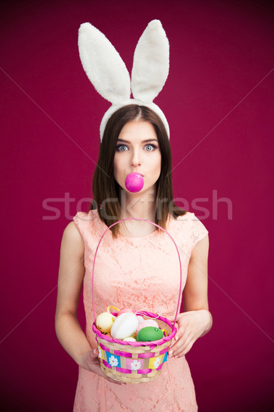 Woman in bunny ears holding Easter egg basket Stock photo © deandrobot