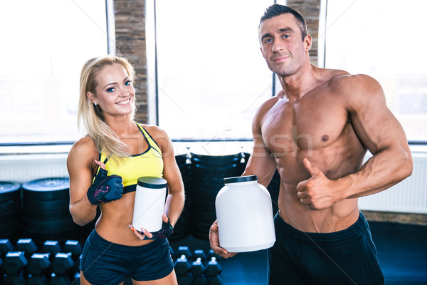 Man and woman holding container with sports nutrition  Stock photo © deandrobot