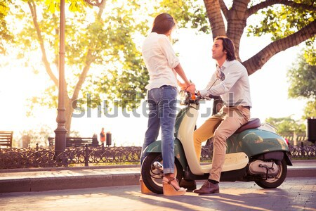 Cheerful young couple riding a scooter and having fun. Sun is shining in the morning Stock photo © deandrobot