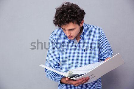 Mérges férfi laptopot használ áll szürke munka Stock fotó © deandrobot