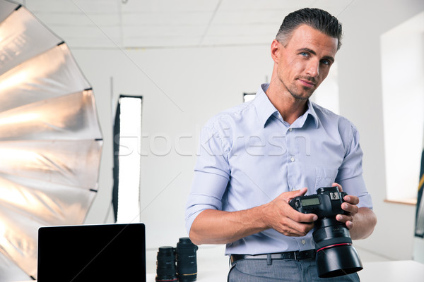 Portrait of a handsome man holding camera  Stock photo © deandrobot