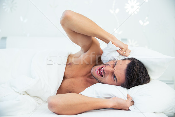 Man lying in the bed Stock photo © deandrobot
