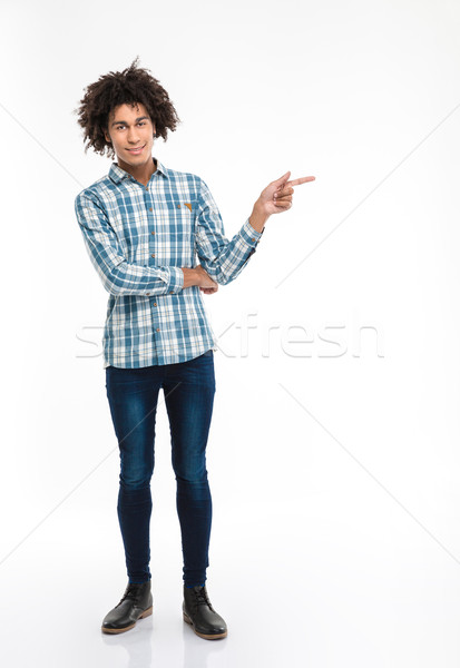 Smiling afro american man with curly hair pointing finger away Stock photo © deandrobot