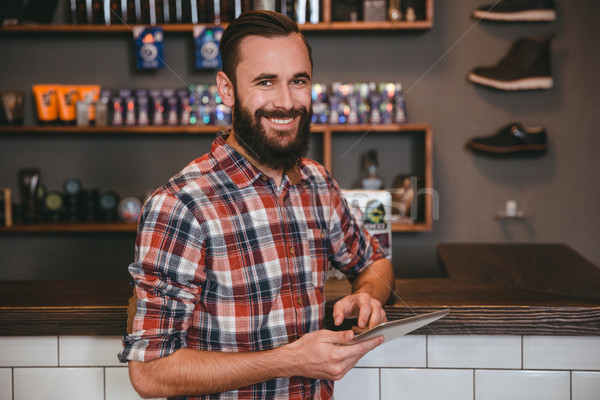 Handsome happy man with beard using tablet in barbershop  Stock photo © deandrobot