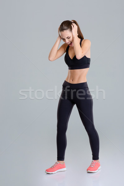 Mad angry fitness girl closed her ears and screaming  Stock photo © deandrobot