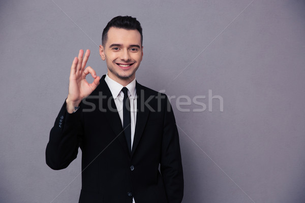Portrait of a smiling businessman showing ok sign  Stock photo © deandrobot