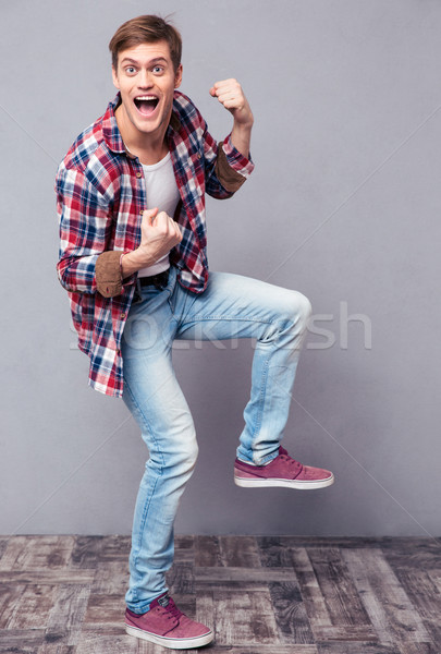 Excited joyful young man in checkered shirt and jeans dancing Stock photo © deandrobot