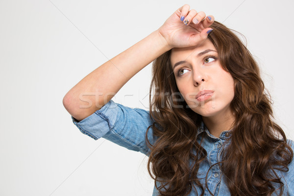 Sad tired young woman with hand on forehead  Stock photo © deandrobot